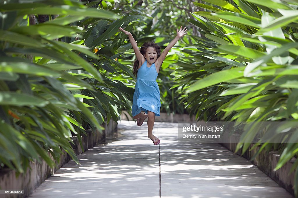 Young happy girl jumping amongst plants : Stock Photo
