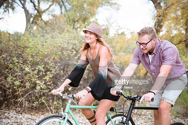 A young, happy man and woman riding bicycles in a park for fitness