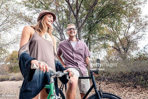 A young, happy man and woman smiling with bicycles in a park for fitness