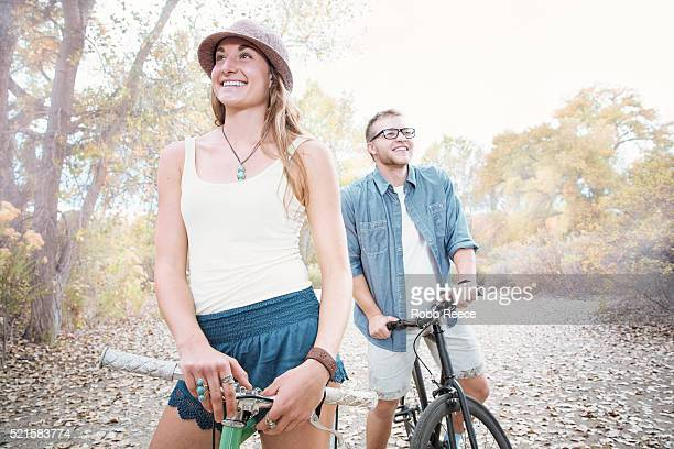 A young, happy man and woman standing with their bicycles in a park