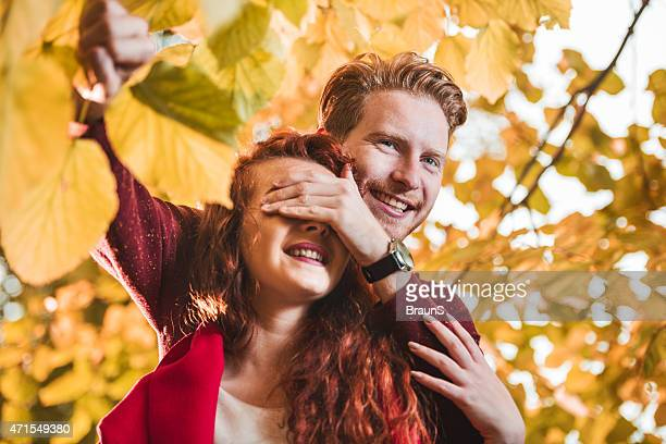 Young happy man covering his girlfriend's eyes in nature.