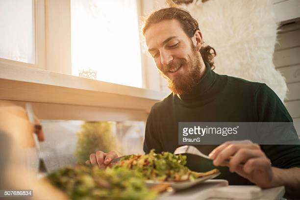 Young happy man enjoying in a healthy meal.