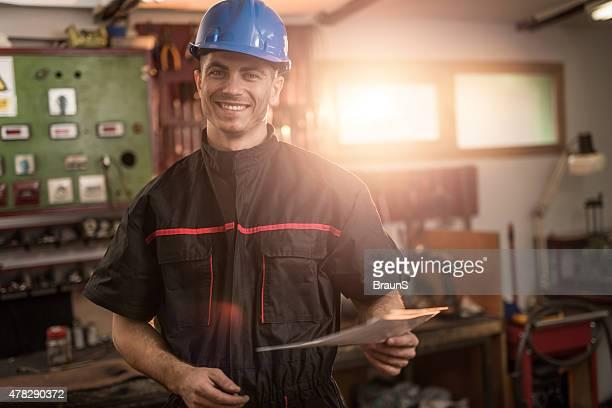 Junge glückliche Arbeiter in die Kamera blickt.