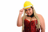 Young happy fat Asian construction woman smiling while holding safety helmet and wearing sexy costume horizontal shot