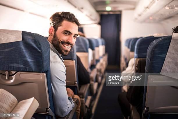 Young happy passenger flying in the airplane.