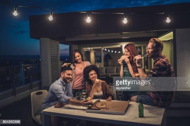 Jeunes gens heureux avoir un dîner de fête pendant la nuit sur une terrasse.