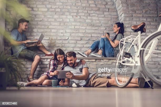 Jonge gelukkige mensen ontspannen tijdens het gebruik van draadloze technologie thuis.