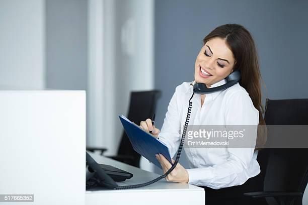 Jeunes heureux secrétaire parlant au téléphone.