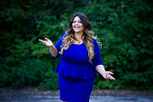 Young happy smiling beautiful plus size model in blue dress outdoors, xxl woman on nature, professional makeup and hairstyle