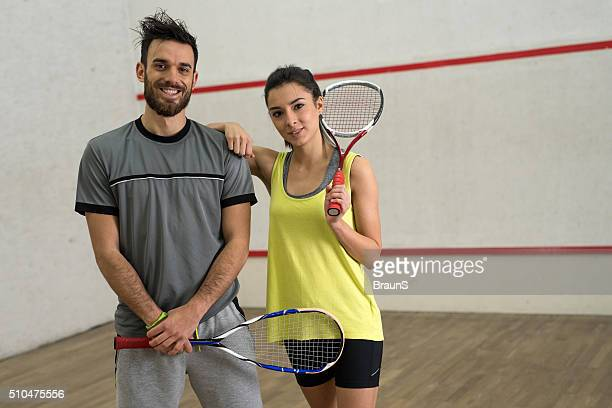 Young happy squash players with rackets on a court.