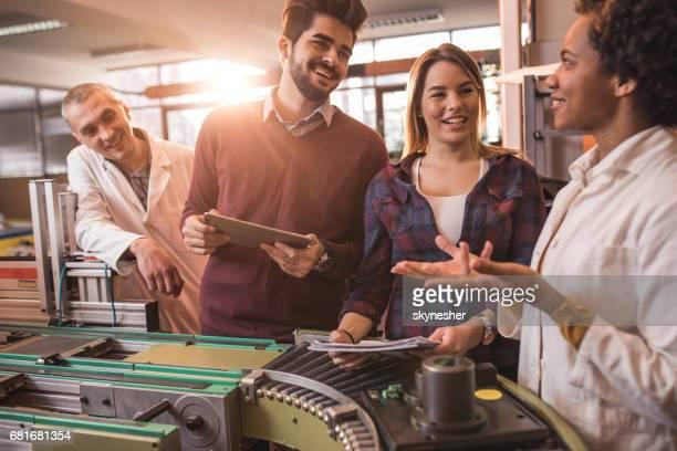 Jeunes étudiants heureux de parler aux ingénieurs dans une usine de fabrication.