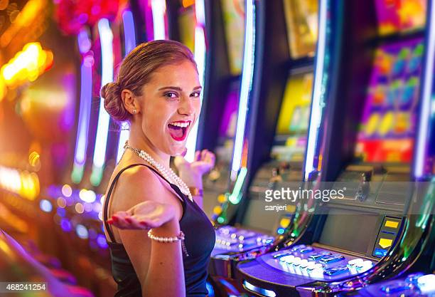 Young happy woman at a casino playing with slot machines