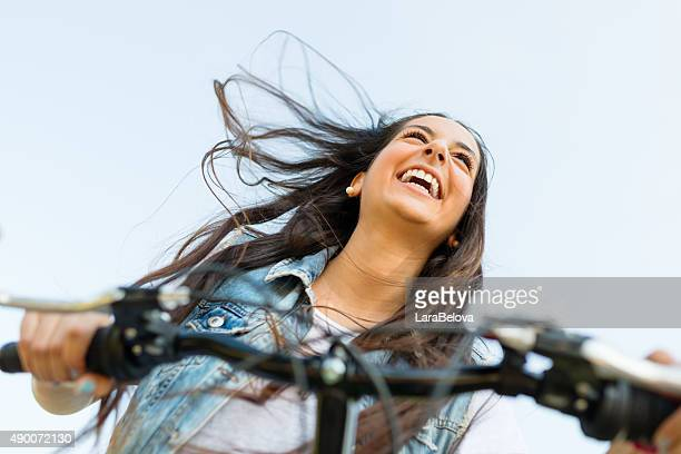 Young happy woman driving a bike