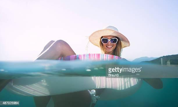 Heureuse jeune femme appréciant le tube flottant en été.