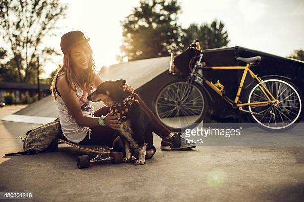 Young happy woman enjoying with dog at skate park.