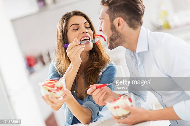 Young happy woman feeding her boyfriend with salad.