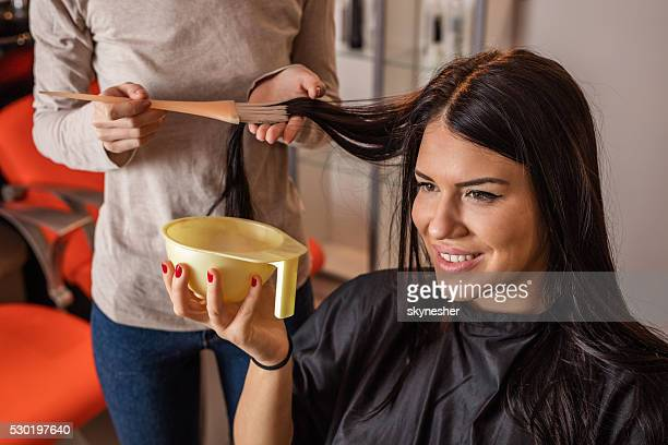 Young happy woman getting her hair dyed at home.