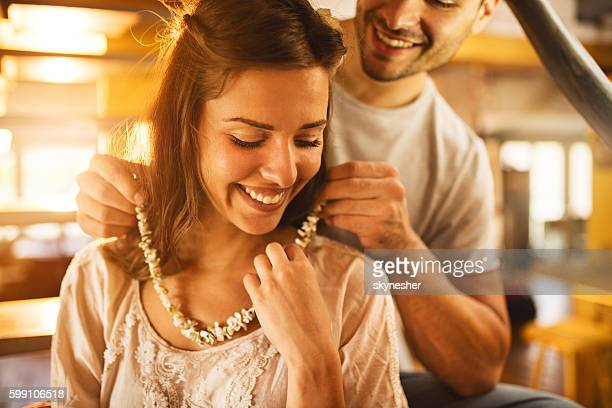Young happy woman receiving a necklace from her boyfriend.