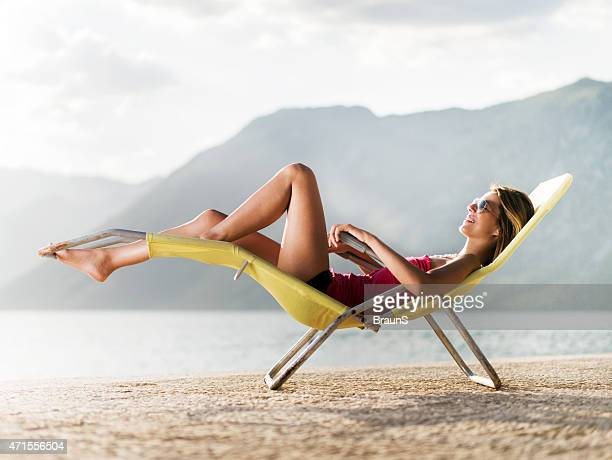 Young happy woman relaxing in deck chair during summer day.