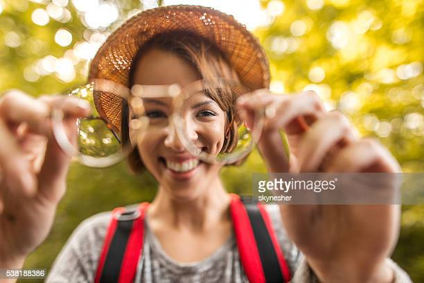 Young happy woman seen through eyeglasses lens in nature.