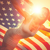 Young happy woman standing in a meadow holding american flag