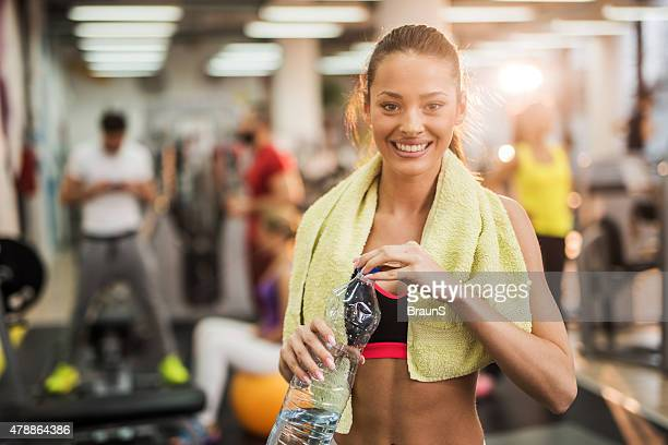 Young happy woman taking a water break in a gym.