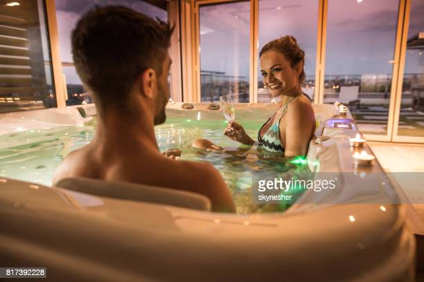 Young happy woman talking to her boyfriend in a hot tub.