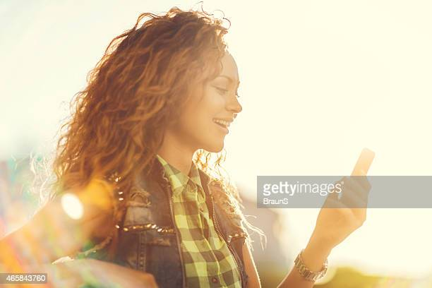 Young happy woman using mobile phone at sunset.