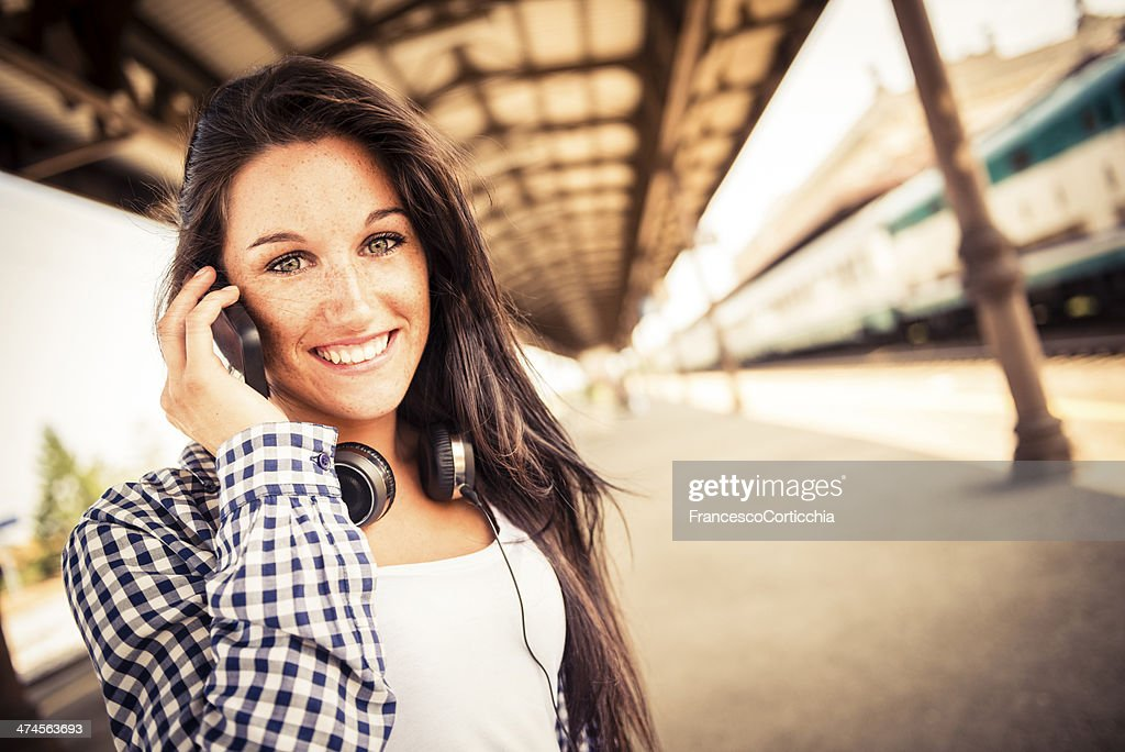 Young happy woman with smart phone at the train station