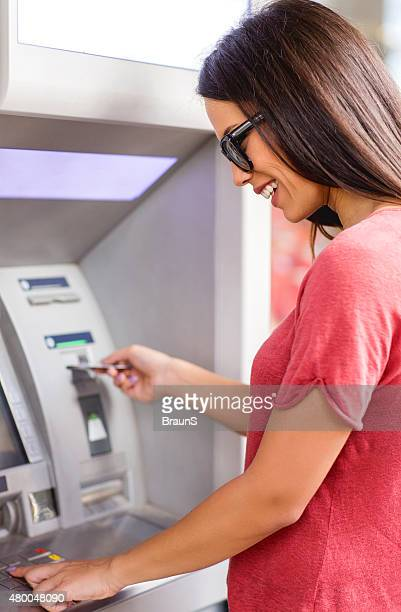 Young happy woman withdrawing money from ATM.