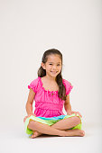 A young Hawaiian preteen adolescent girl in a dress posing on white background.