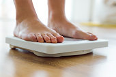 Portrait of young healthy girl on home scales.