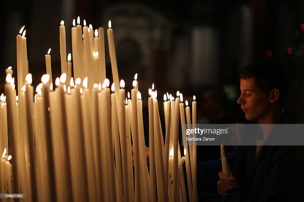 A young helper arranges candles inside the Church during the Santa Maria Della Salute celebrations on November 21, 2012 in Venice, Italy. During the annual Santa Maria Della Salute celebrations, Venetians make pilgrimage to the Church to give thanks to the Virgin Mary (Maria), who is believed to have brought an end to the plague which struck the city in 1629.