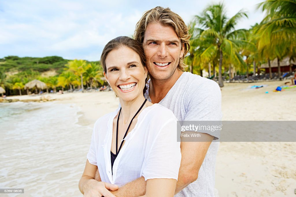 Young heterosexual couple embracing on beach : Stock Photo