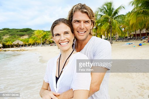 Young heterosexual couple embracing on beach : Photo