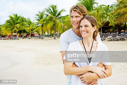 Young heterosexual couple embracing on beach : Foto stock