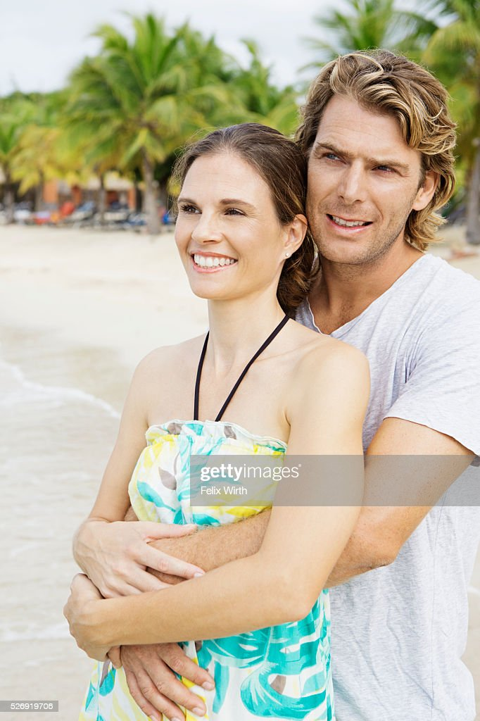 Young heterosexual couple embracing on beach : Stock-Foto
