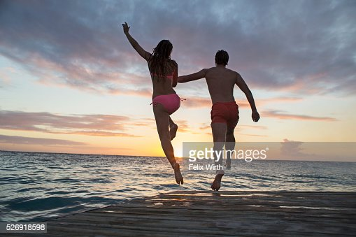 Young heterosexual couple jumping into water at sunset : ストックフォト