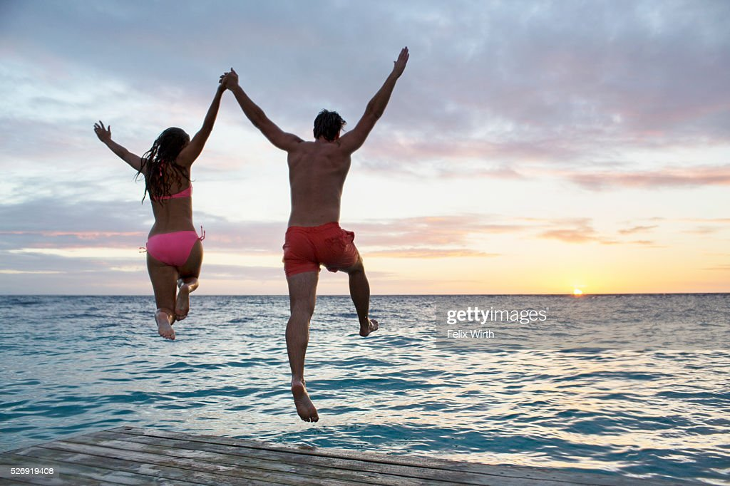 Young heterosexual couple jumping into water at sunset : Foto de stock