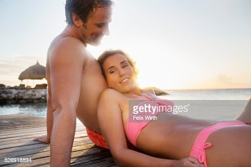 Young heterosexual couple relaxing on beach : Stock-Foto