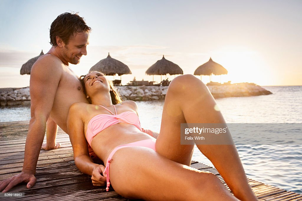 Young heterosexual couple relaxing on beach : Stock Photo