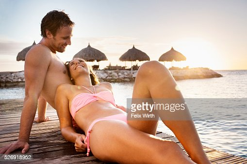 Young heterosexual couple relaxing on beach : ストックフォト