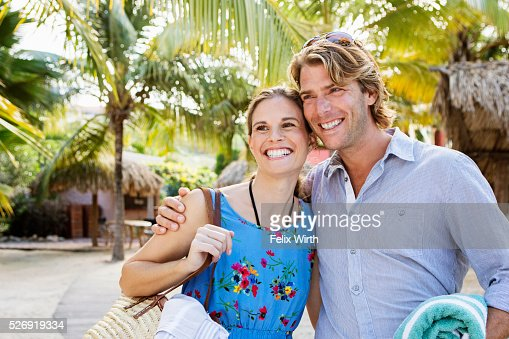Young heterosexual couple standing on beach : Stock Photo