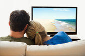 Young heterosexual couple watching television on t