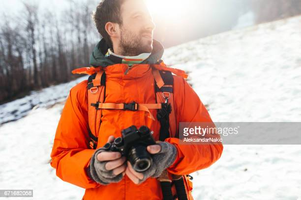 Young hiker in nature holding his camera