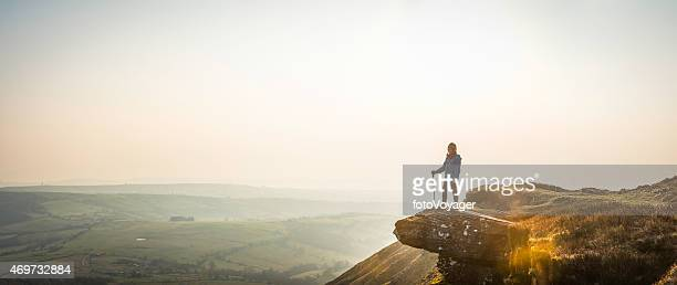 Young hiker looking out over mountain valley misty dawn panorama