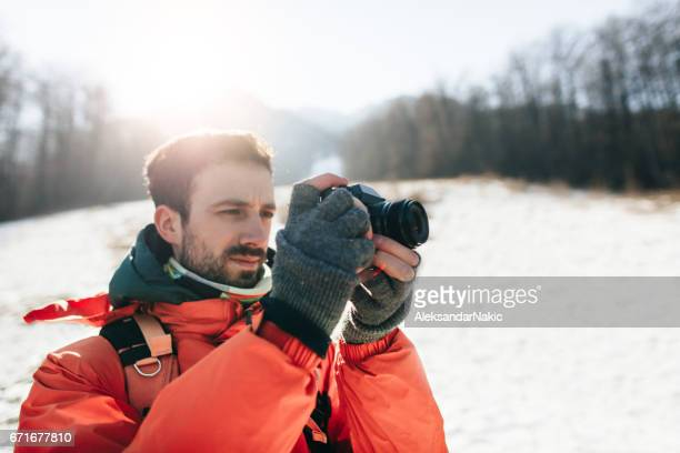 Young hiker photographing winter landscape