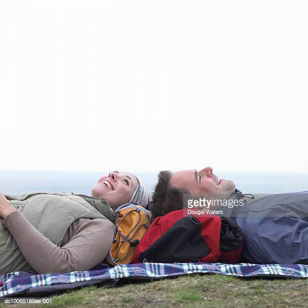 Young hikers in countryside, laying on rug