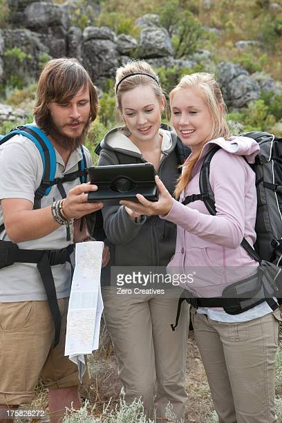 Young hikers looking at hand held computer