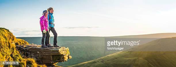 Junge Wanderer auf Berg top mit Blick auf das goldene Sonnenlicht Landschaft panorama